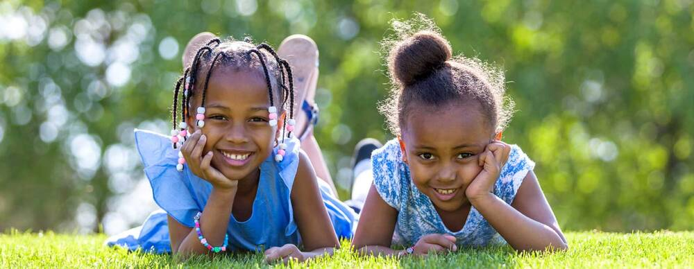 2 children laying in the grass smiling