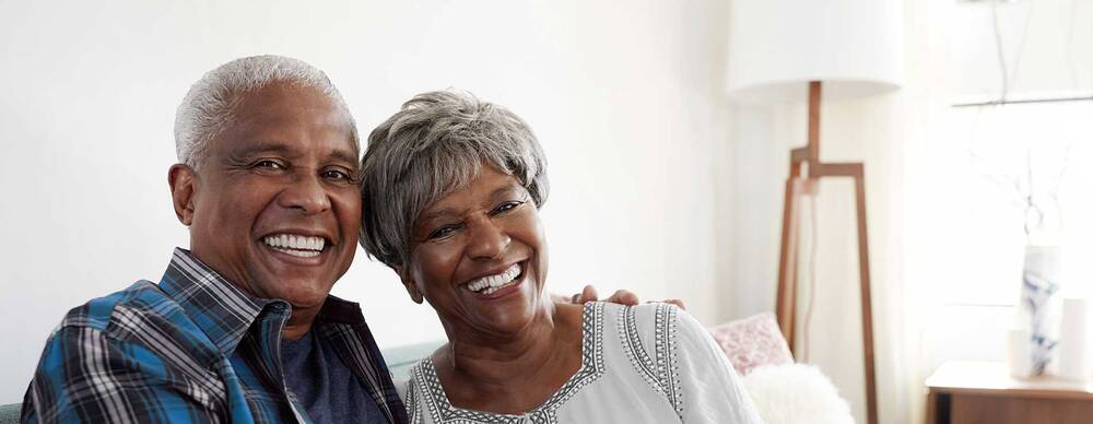 Elderly couple smiling on couch